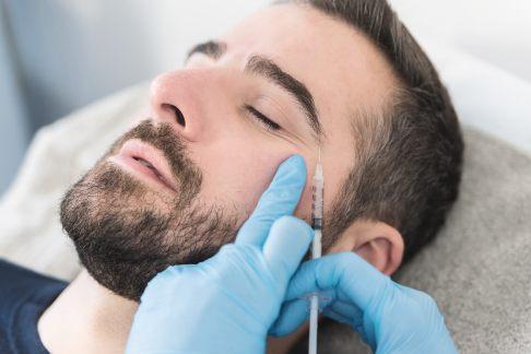 Mann erhält Botox-Injektion gegen Krähenfüße