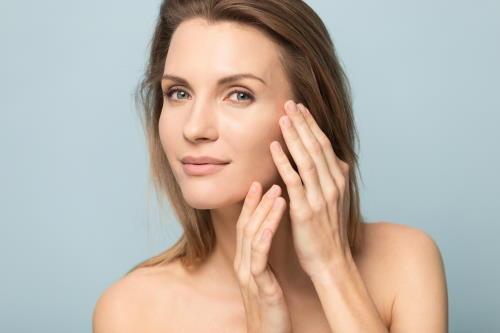 Zufrieden blickende Frau mit glattem Gesicht nach einer Hautbehandlung.