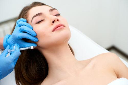 Arzt injiziert Botox in den Kaumuskel einer Patientin.