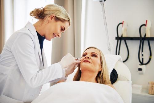 Ärztin injiziert Botox in die Wange einer Patientin.