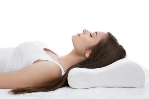 Frau schläft auf einem Nackenkissen.